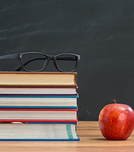Eyeglasses on top of stacked books on a table next to an apple and in front of a chalkboard