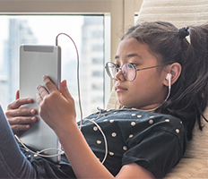 Girl wearing headphones and using a tablet