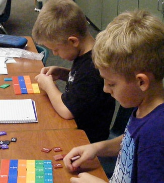 Two students use blocks in a class project