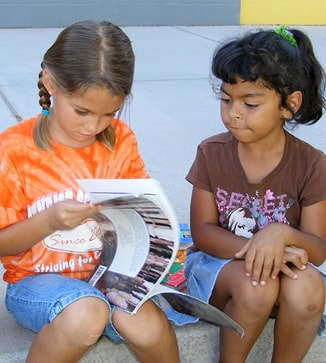 Two students flip the pages of a book outside