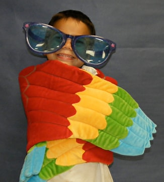 Student wearing parrot wings and big sun glasses poses