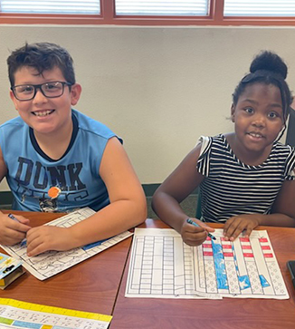 Teacher poses with students in a classroom
