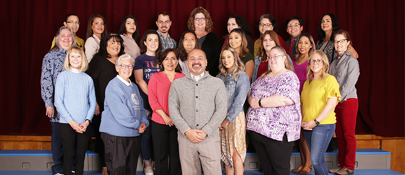 Five smiling kids sitting on a playground bridge