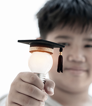 School boy holding up a light bulb with graduation hat