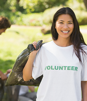 Happy woman in volunteer t-shirt helping with yard work