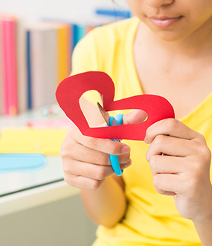 School girl cutting out a red-shaped paper heart