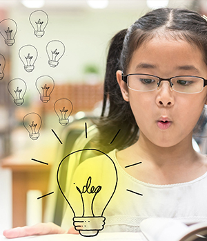 School girl looking at a light bulb graphic