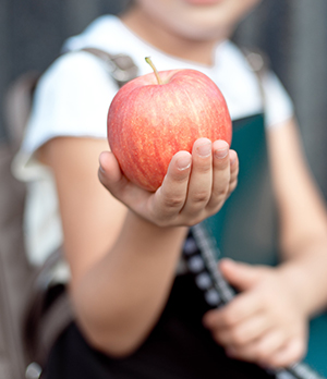 School girl holding out an apple