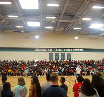Students and staff members in the gym under a sign reading Home of the Bulldogs