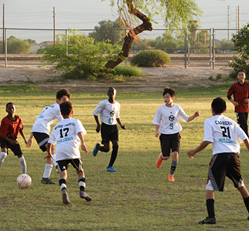 Male students play soccer together outside with another team
