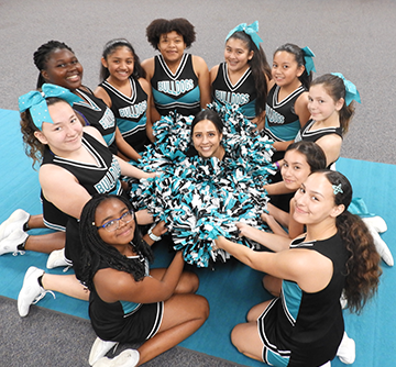 Cheerleaders pose in a circle with their pom poms