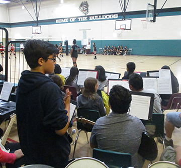 School band members watch a volleyball game in the gym