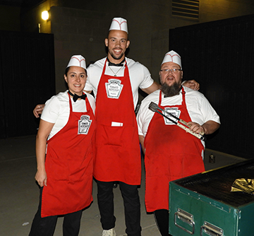 Three staff members wearing Heinz Tomato Ketchup aprons and food preparation hats pose together beside a grill