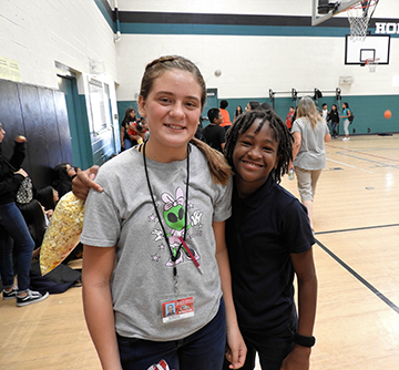 Two students pose together in the gym as one student holds a bag of popcorn