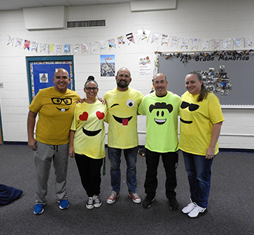Five staff members wearing emoji t-shirts pose together in a classroom