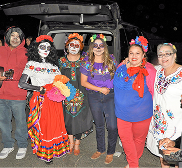 Students, their family members and staff members dressed as Coco characters pose together