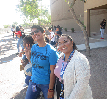 A smiling female student poses outside with a female student holding up a peace sign with her fingers