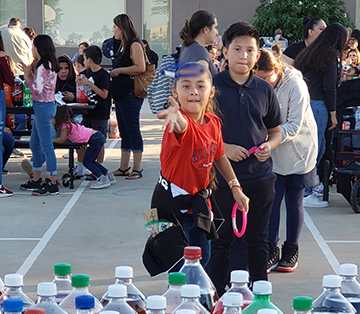 Students playing a toss game at school fair