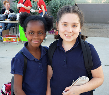 Two happy WVES school girls in navy shirts