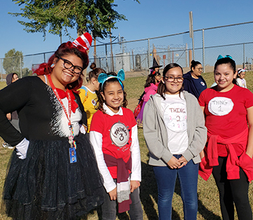Teacher dressed up with students in Dr. Seuss attire