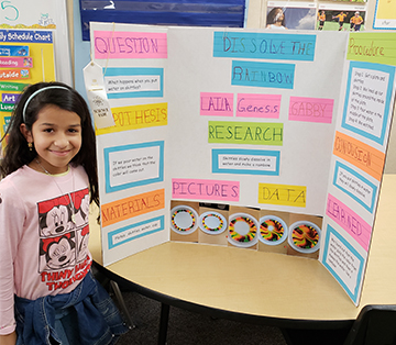 Proud school girl in front of poster project