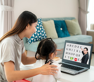 Mom helping daughter at home with online learning