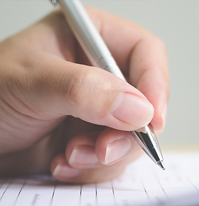 Hand with pen signing a paper