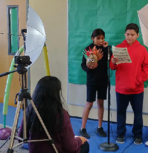 Two students presenting in front of a video camera