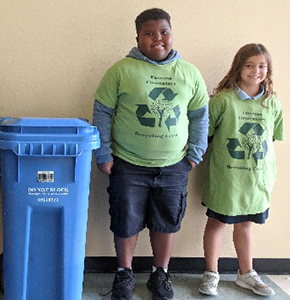 Two students next to recycle bin wearing recycle t-shirts
