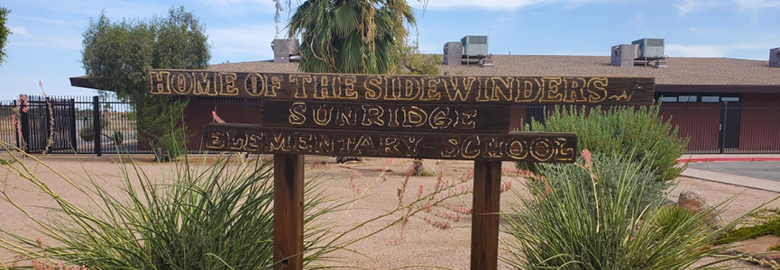 A wooden welcome sign saying Home of the Sidewinders - Sunridge Elementary School