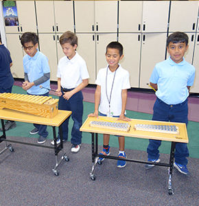 Sunridge students standing with musical instruments in hallway