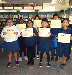 Group of students holding up certificates