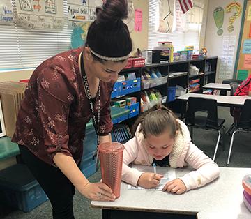Teacher helping a student at her desk