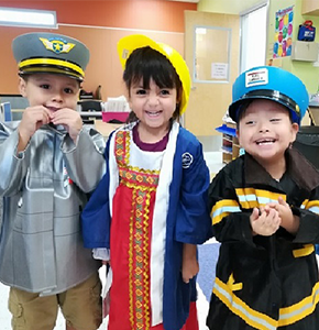 Three students dressed in career outfits pose together