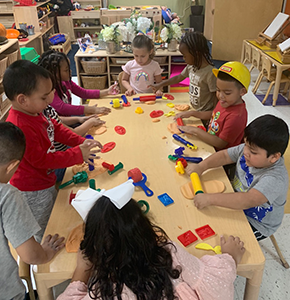 Group of students playing with Play Doh, roller pins and dough cutters in a classroom