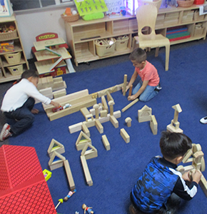 Three students playing with blocks on a classroom floor