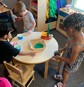 Three students playing with Play Doh around a table in a classroom
