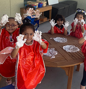 Group of students wearing smocks hold up their hands covered in whipped cream