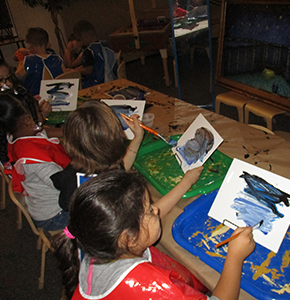 Four students in a classroom paint together