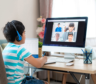 Elementary school boy video conferencing with classmates