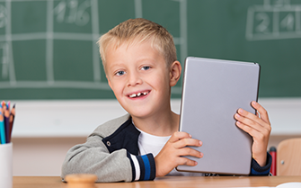Boy with tablet in classroom