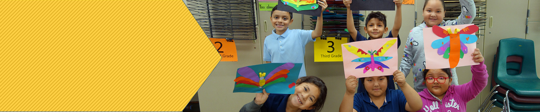 Students at Fowler Elementary holding up their artwork.
