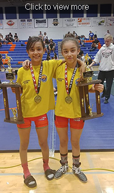 Click to view more. Two students display their medals and trophies.