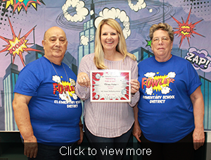 Tiffany Fisher holds up her principal for a day certificate as she stands next to two staff members