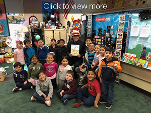 Staff member wearing a Cat in the Hat hat holds up a copy of Oh, The Places You'll Go as he poses with students in a classroom