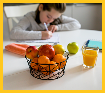 Bowl of fruit and a glass of orange juice in front of a female student writing on a piece of paper