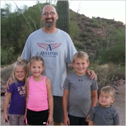 Four kids and an adult pose in front of a cactus