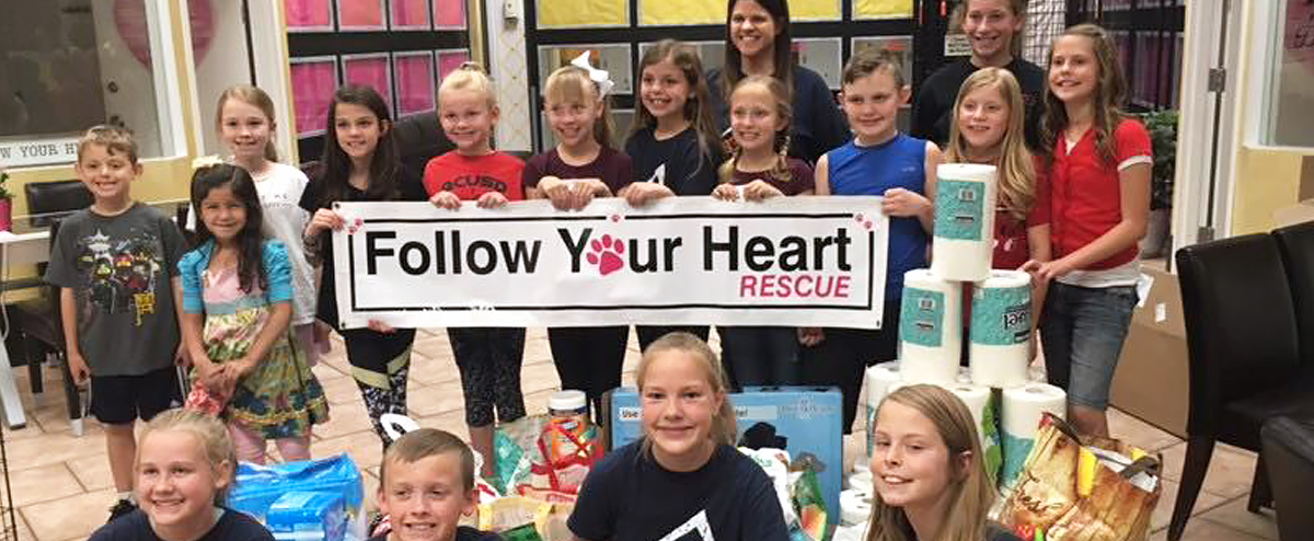 A group of students hold a sign reading Follow Your Heart Rescue