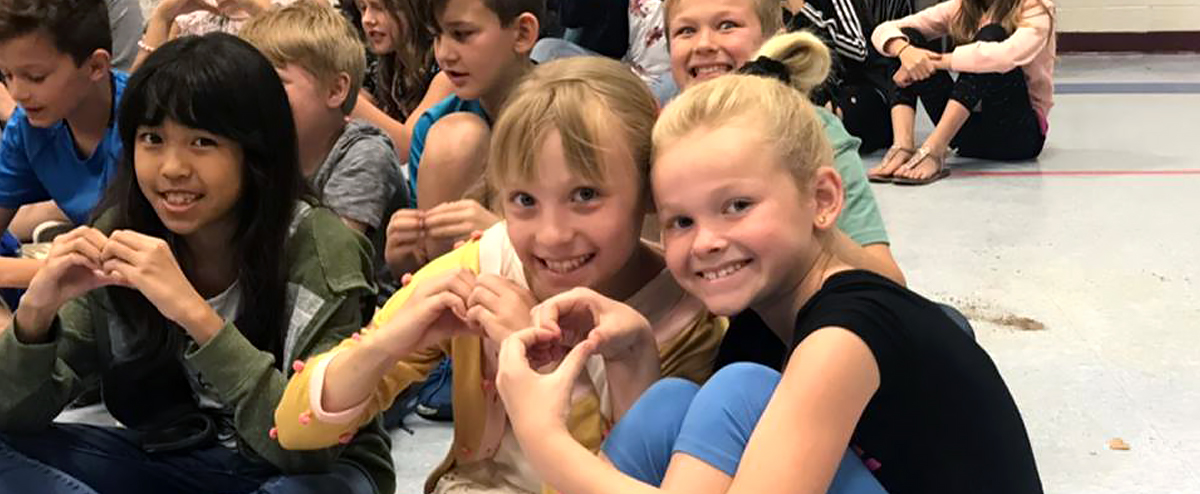 Smiling students form heart shape with hands