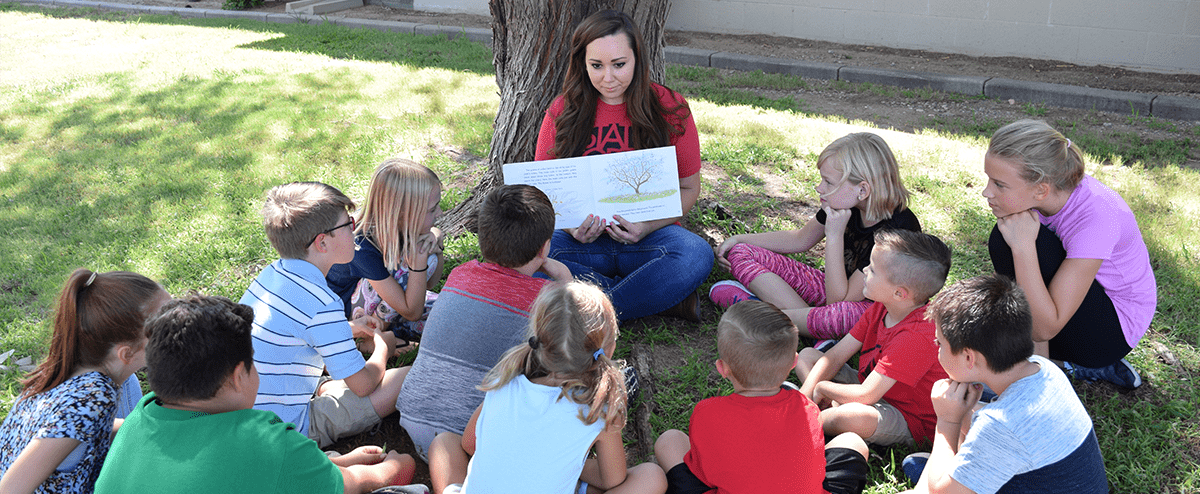 Teacher reading to students underneath a tree